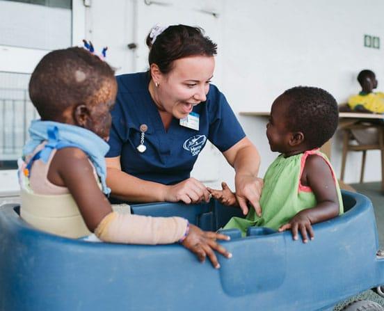 Eine Krankenschwester spielt mit zwei Kindern