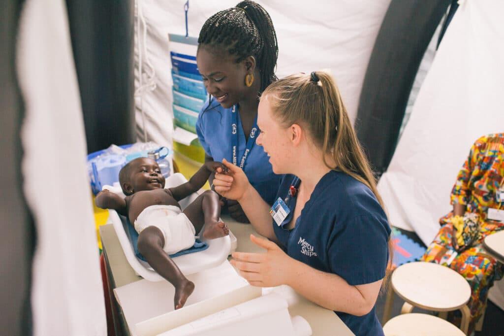 Fatou mit zwei Krankenschwestern beim Wiegen