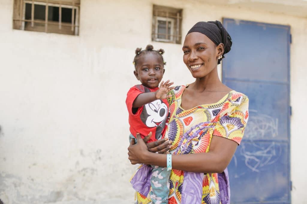 MKG Patientin Fatou winkt auf dem Arm ihrer Mutter