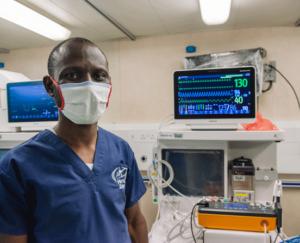 Medizintechniker Emmanuel Essah mit Maske vor einem Monitor