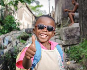 Junger Grauer Star Patient freut sich nach Operation mit Sonnenbrille