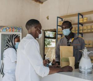 Birima, Food for Life Teilnehmer aus dem Senegal bedient Kunden in seinem Lebensmittelladen