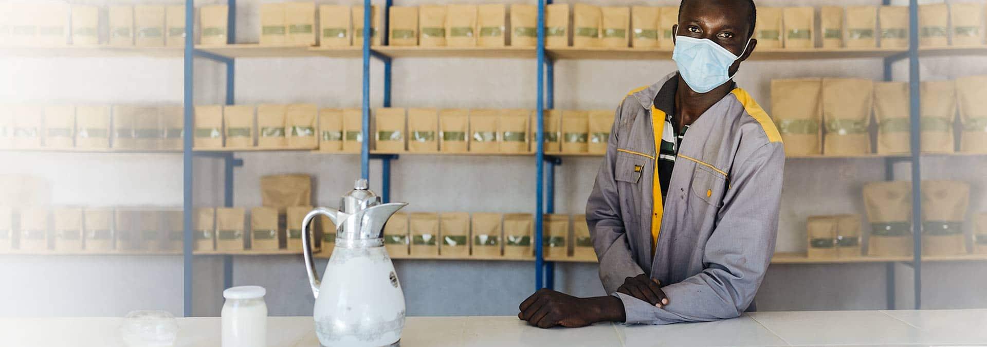 Birima, Food for Life Teilnehmer aus dem Senegal bedient Kunden in seinem Lebensmittel-Laden